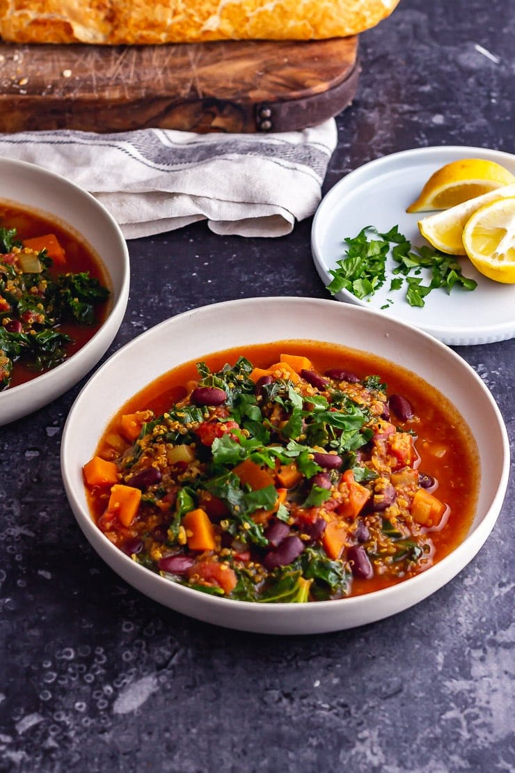 White bowl of vegan stew on a dark background