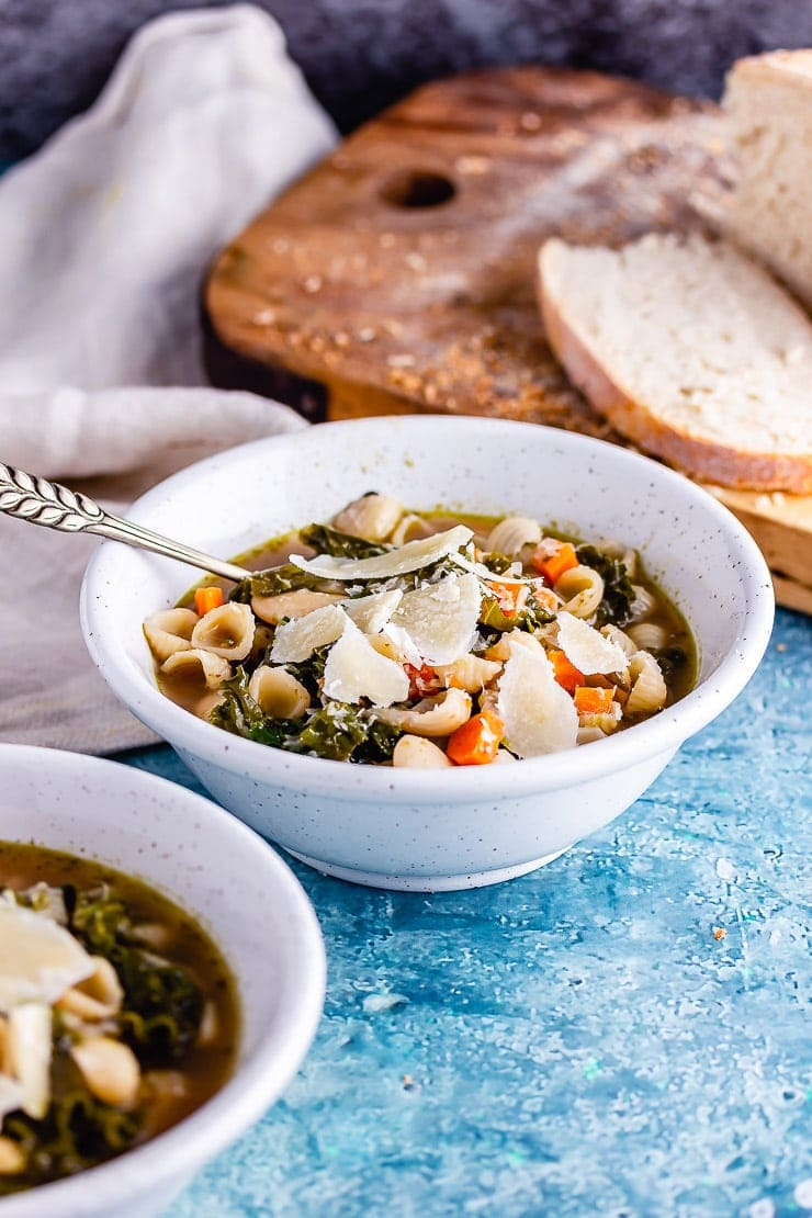 Bowl of veggie pesto pasta soup with bread on a board in the background