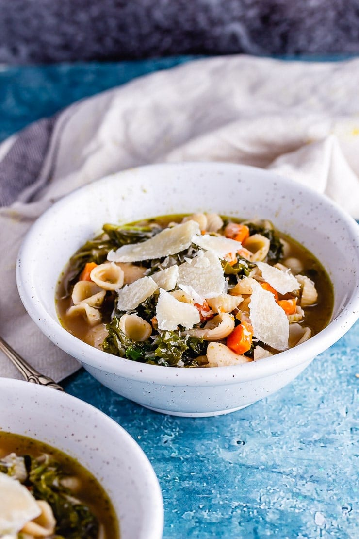 White bowl of veggie pesto pasta soup with a pale cloth