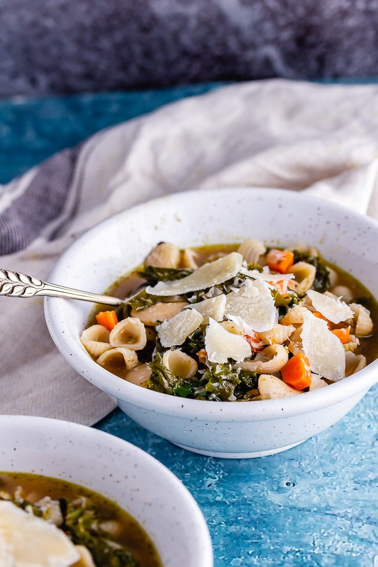 Bowl of veggie pesto pasta soup with a pale cloth and a spoon