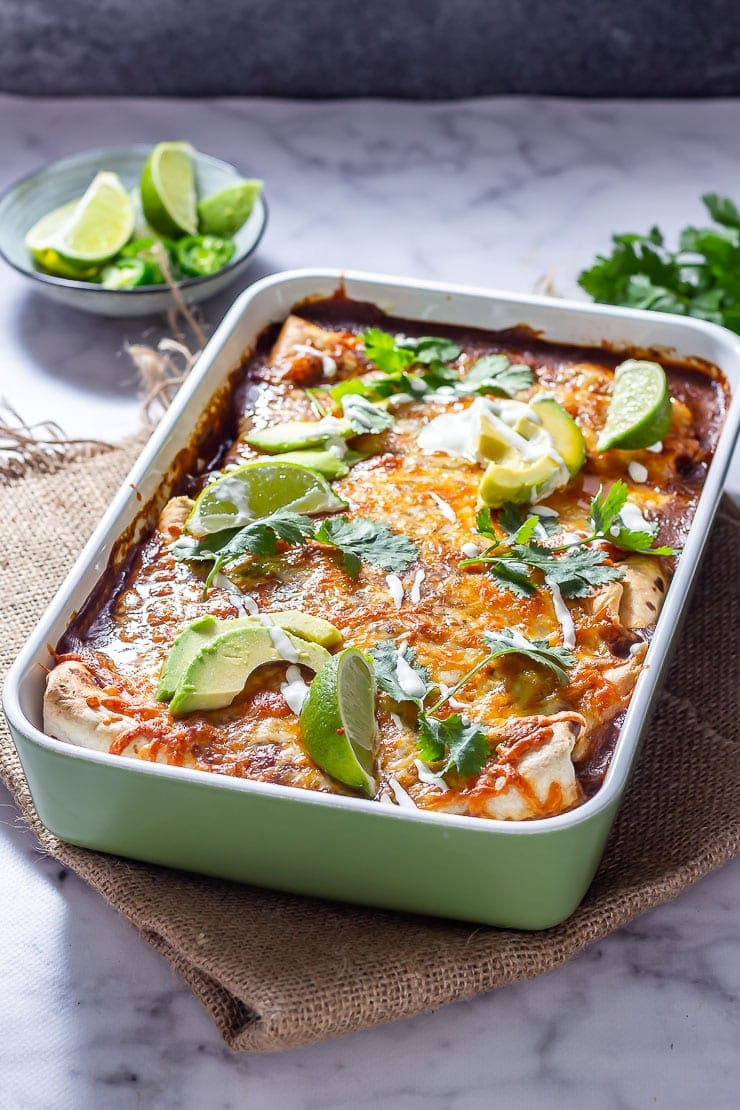 Side on shot of vegetarian enchiladas in a green baking dish on a mat