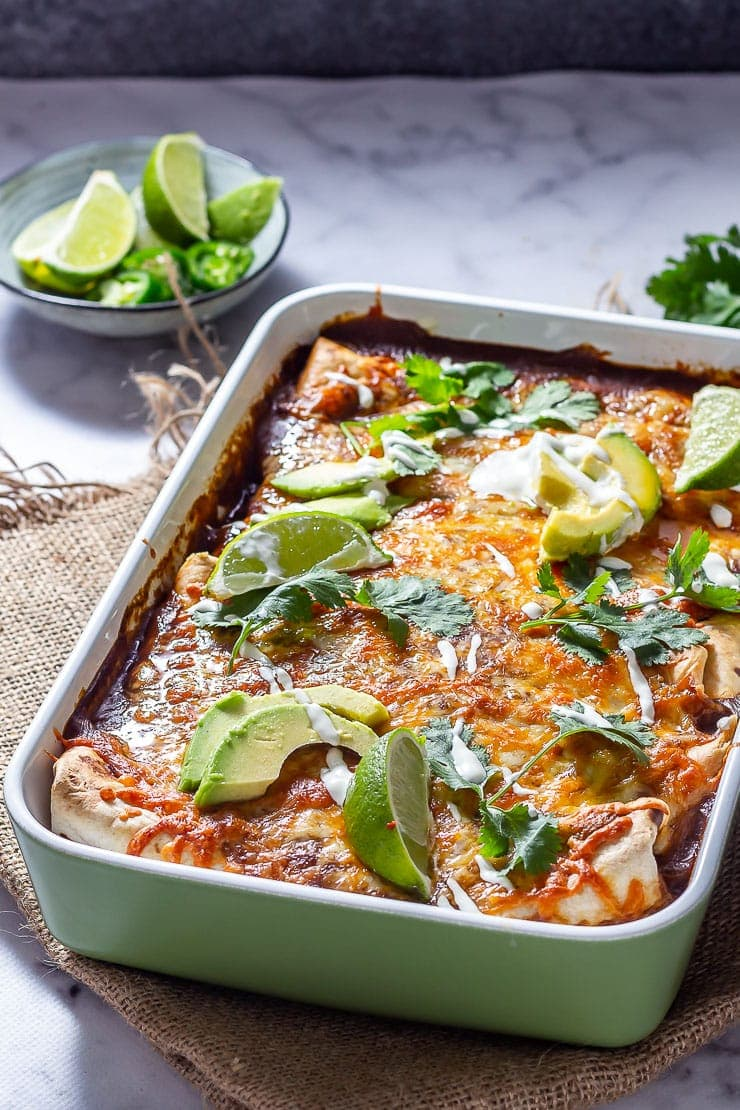 Side on shot of vegetarian enchiladas in a green baking dish on a marble background with lime