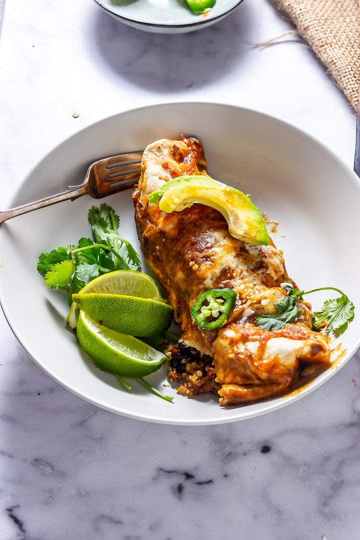 Vegetarian enchilada with lime and herbs in a bowl on a marble background