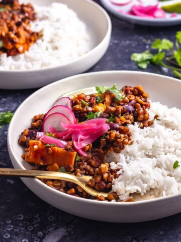 Side on shot of veggie chilli with rice in a white bowl on a dark background