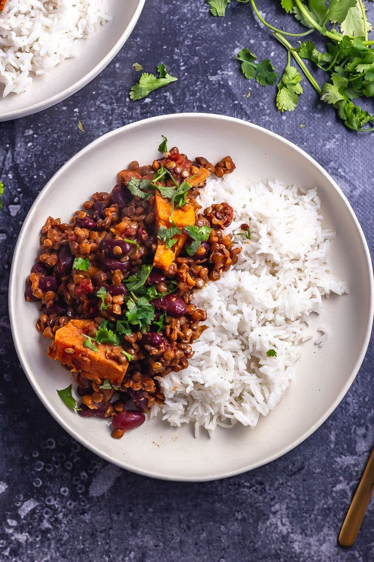 Overhead shot of a white bowl of veggie chilli with rice on a grey background with coriander