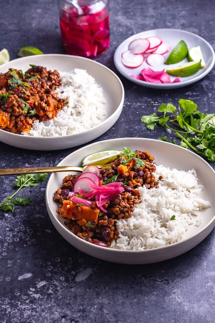 Two bowls of veggie chilli on a dark background with toppings
