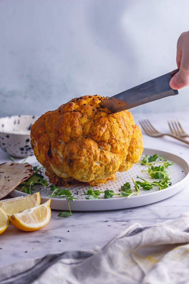 Whole roasted cauliflower with a knife cutting it