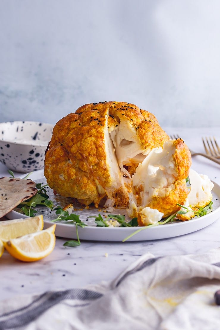 Whole roasted cauliflower with a slice cut from it on a marble background