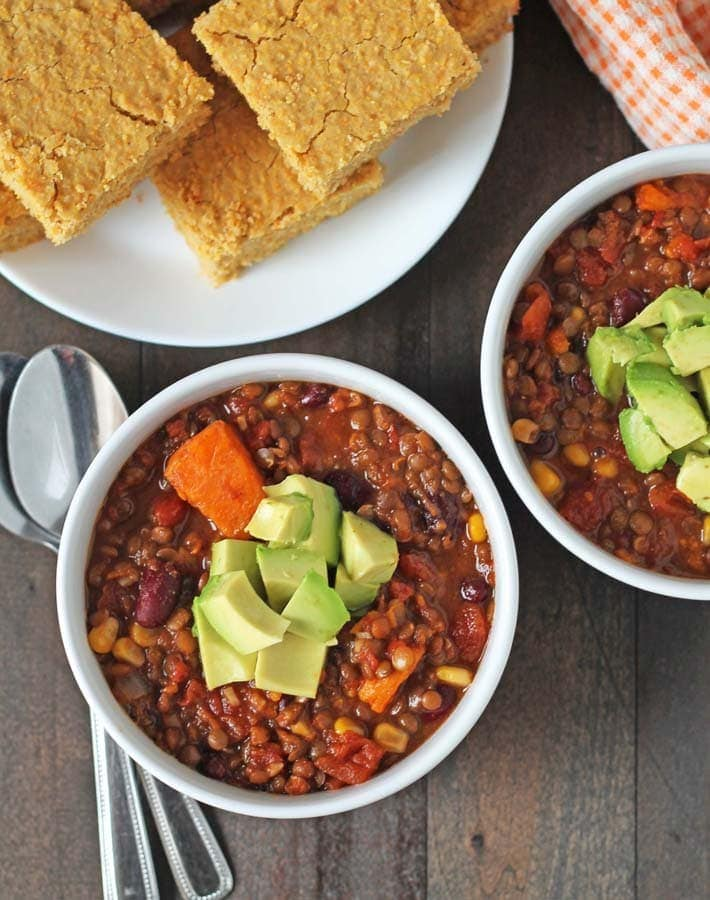 Overhead shot of lentil sweet potato chilli with cornbread for vegan comfort food round up
