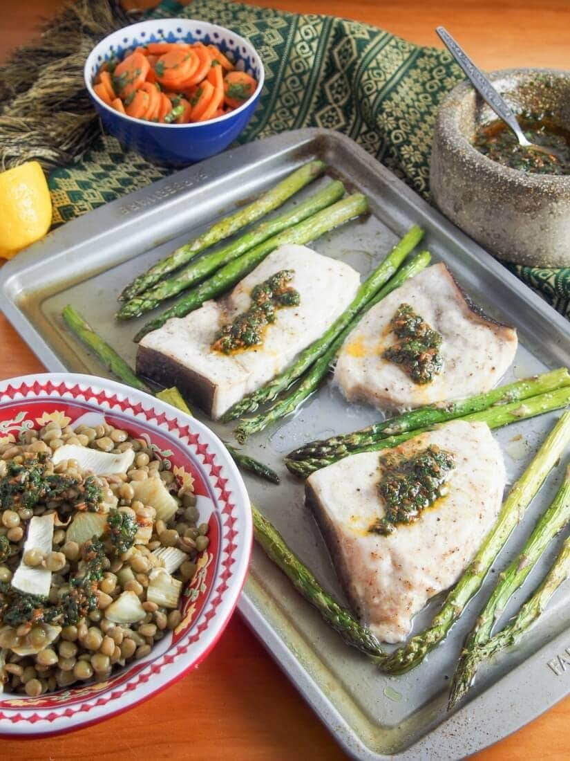 Baked swordfish and asparagus on a baking sheet