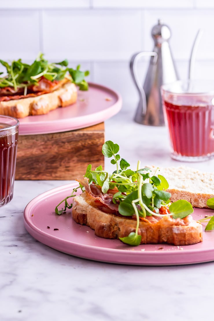 Breakfast sandwich topped with watercress on a pink plate on a marble surface