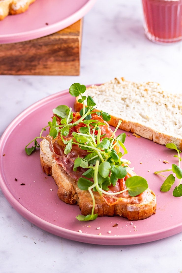 Open breakfast sandwich topped with watercress on a pink plate