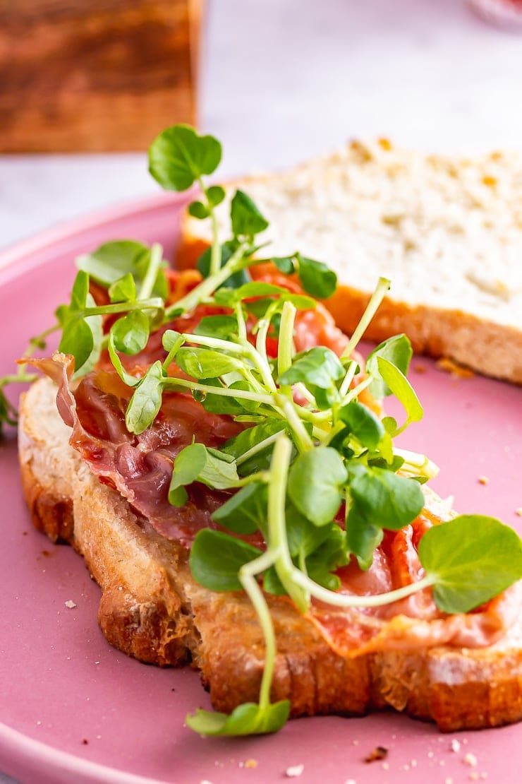 Watercress on a breakfast sandwich on a pink plate