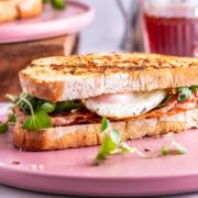 Side on shot of breakfast sandwich on a pink plate
