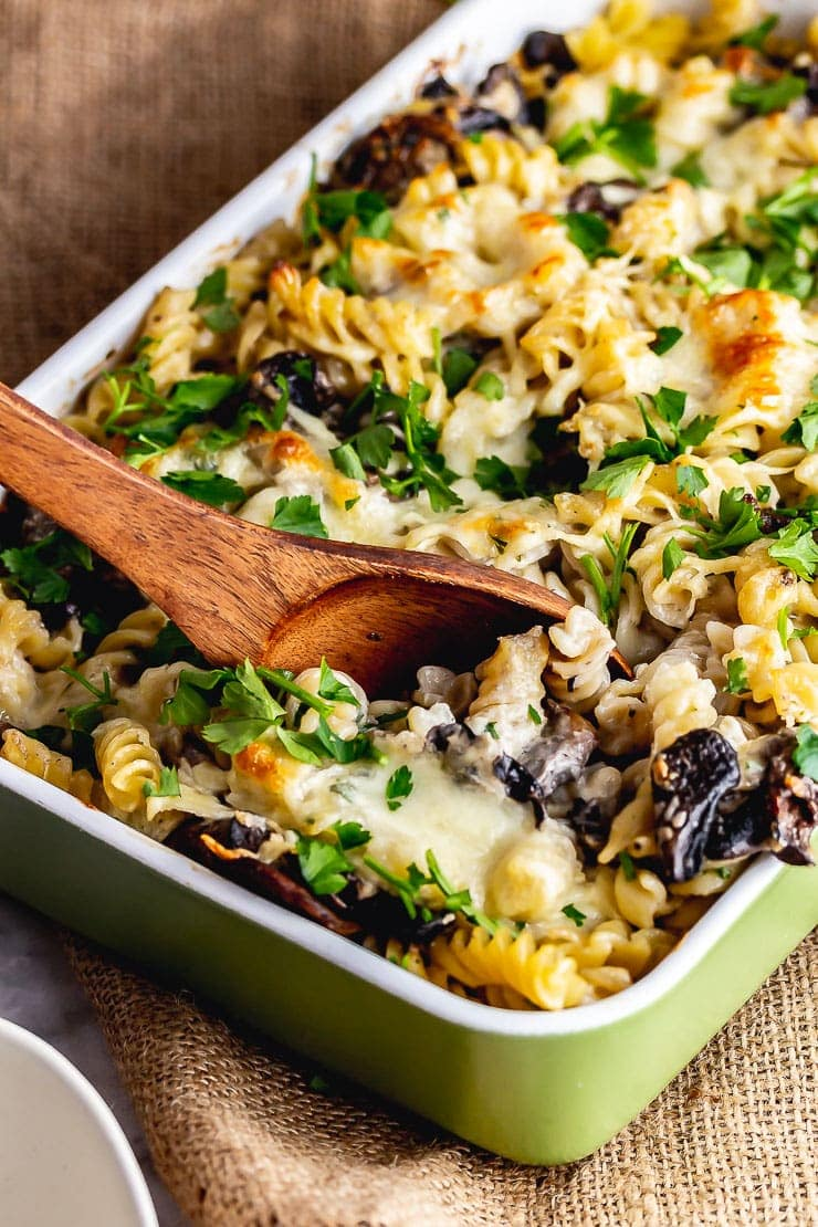 Wooden spoon in creamy mushroom pasta bake on a woven mat
