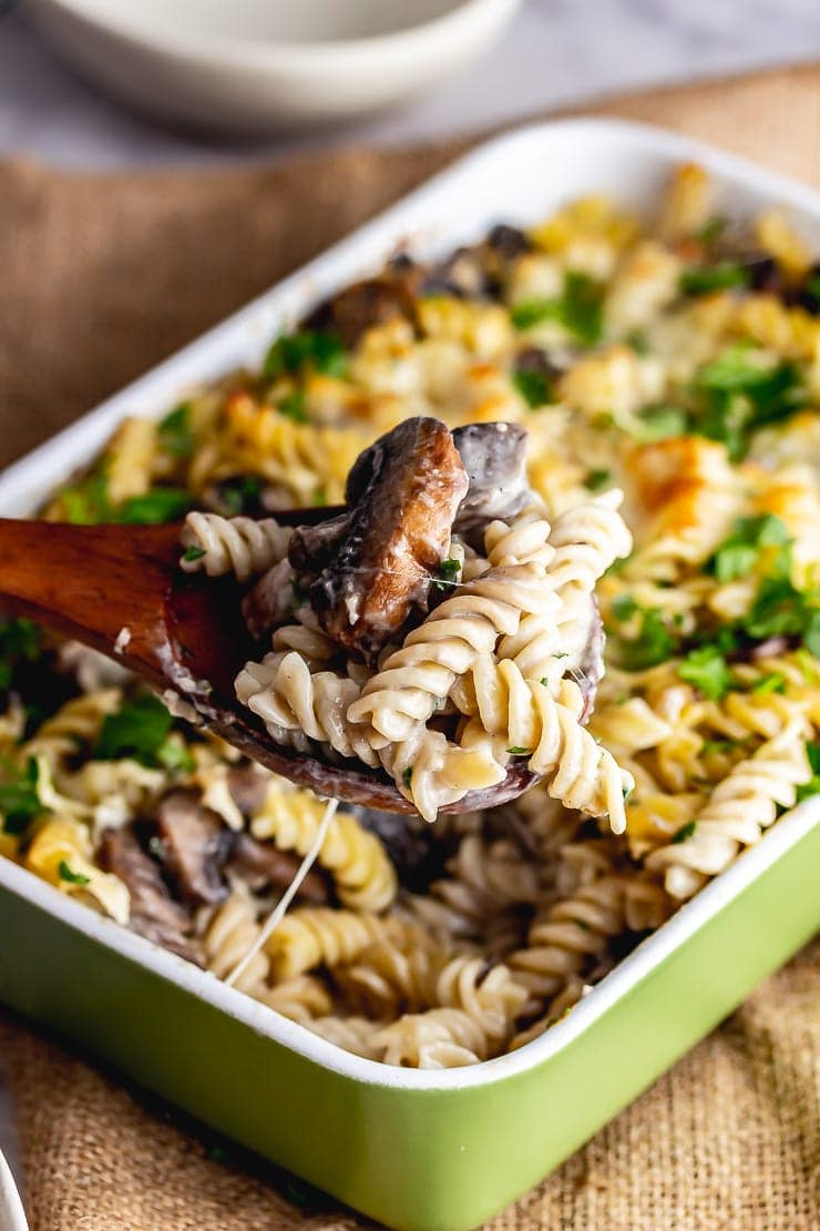 Wooden spoon taking a portion of creamy mushroom pasta bake