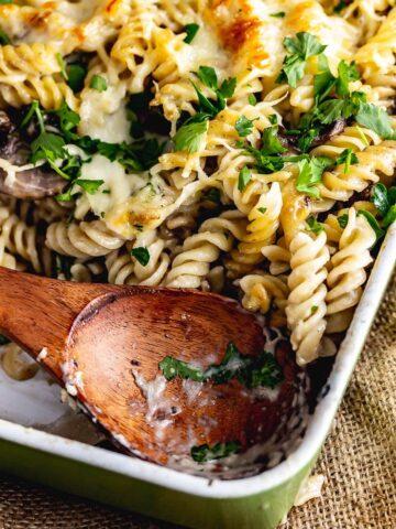 Wooden spoon in a creamy mushroom pasta bake