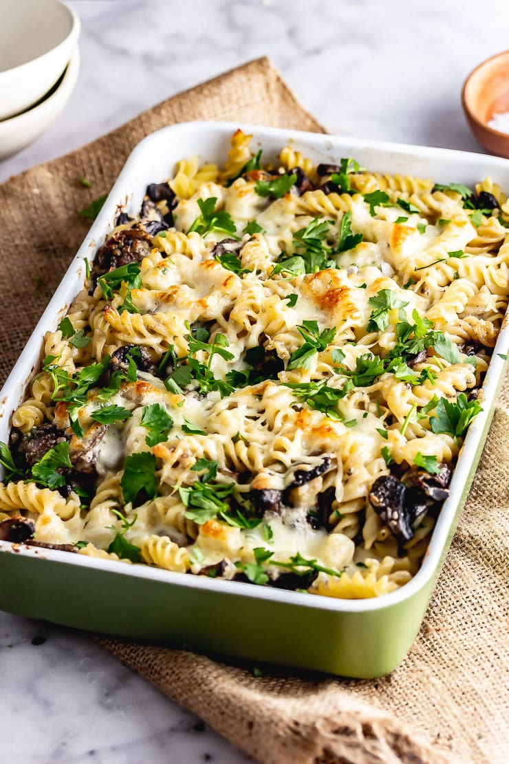 Green baking dish of creamy mushroom pasta bake on a mat