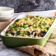 Green baking dish of mushroom pasta bake on a hessian mat over a marble surface