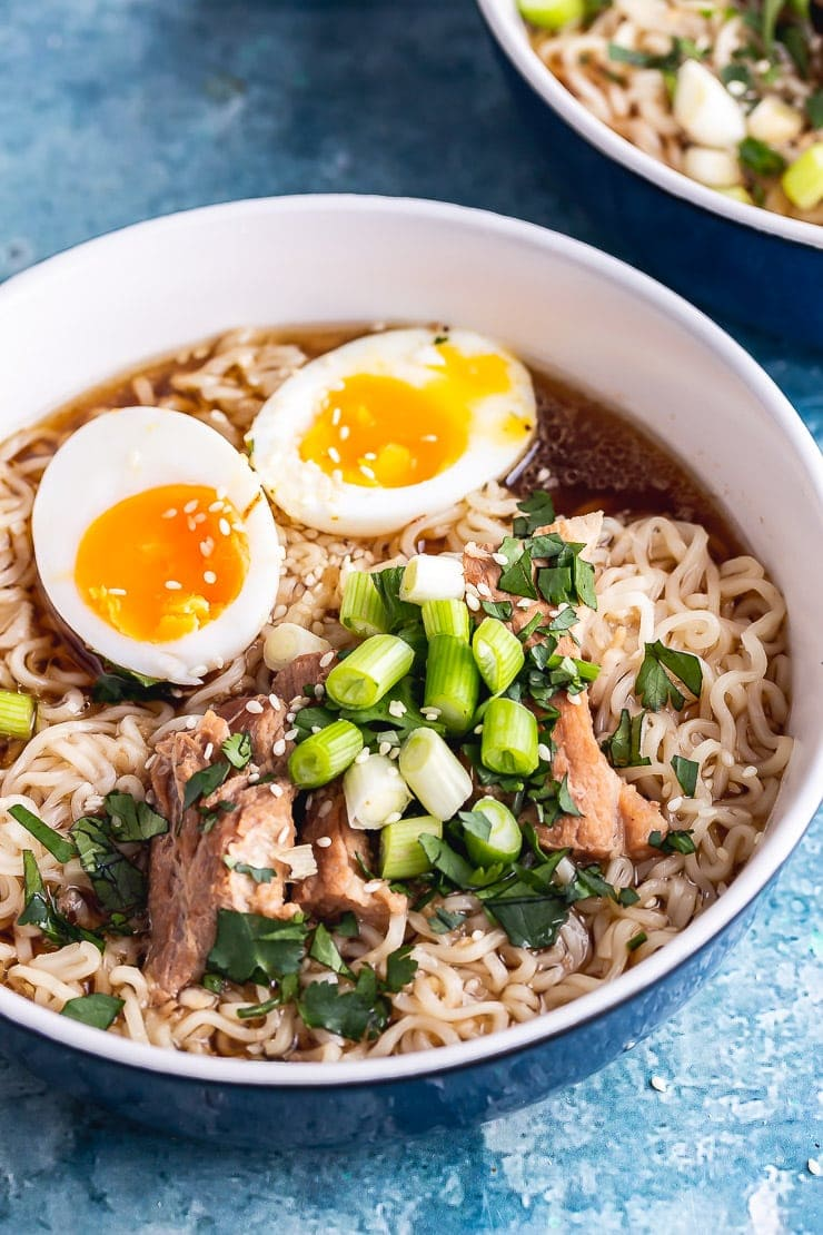 Close up of pork ramen topped with spring onions and a boiled egg