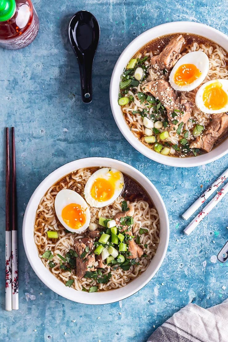Overhead shot of two bowls of pork ramen with spoons and chopsticks