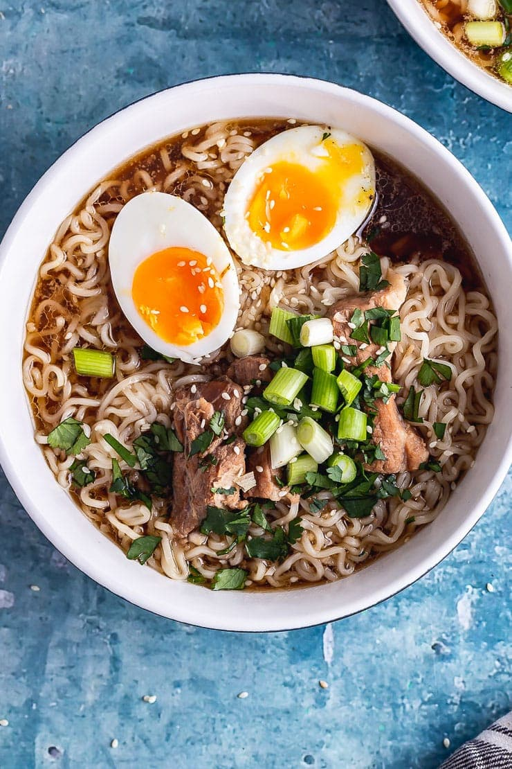 Overhead shot of pressure cooker pork ramen with an egg on a blue background