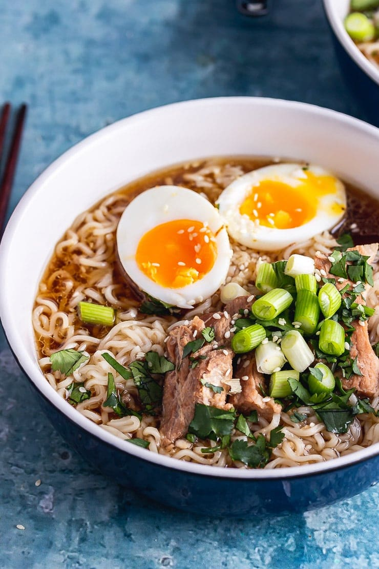 Close up of pork ramen in a blue bowl with a boiled egg
