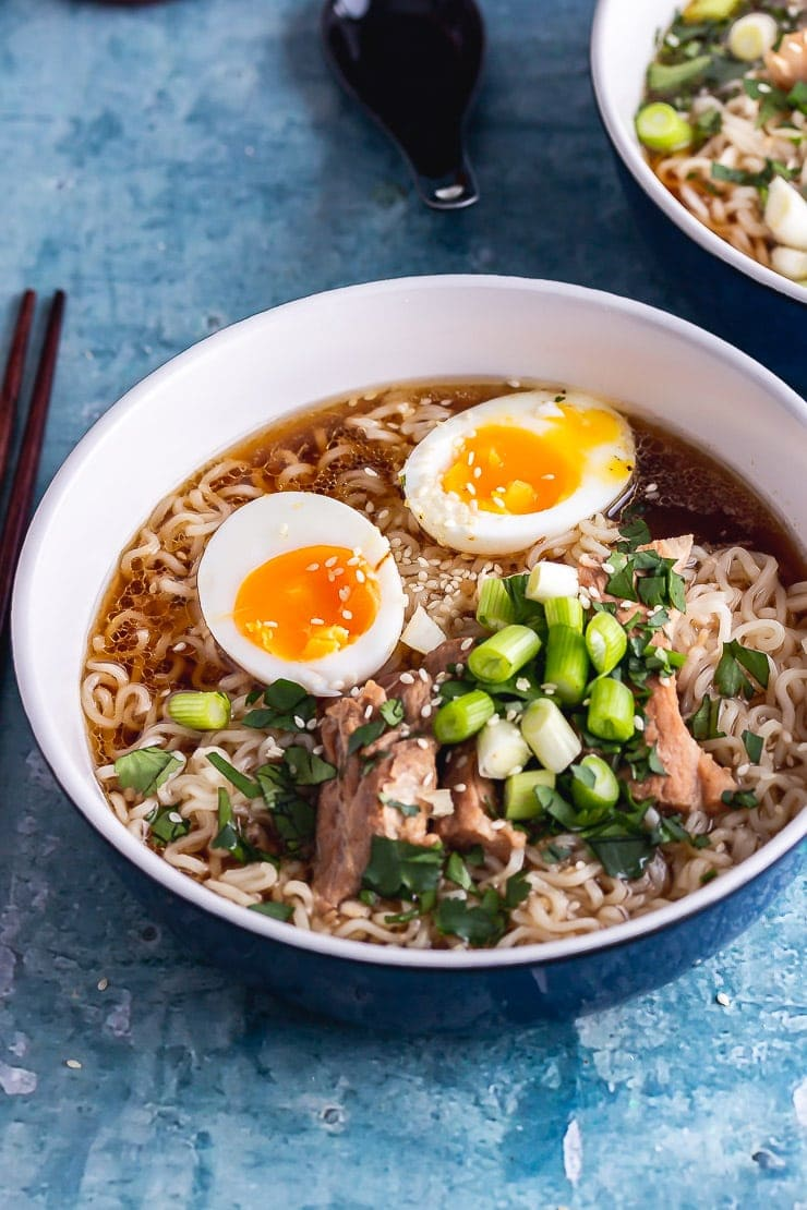 Blue bowl of pork ramen with toppings on a blue background