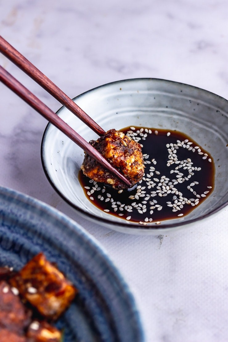 Chopsticks dipping salt and pepper tofu into soy sauce