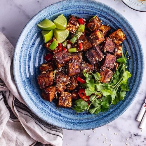 Overhead shot of salt and pepper tofu in a blue bowl with toppings on a marble background
