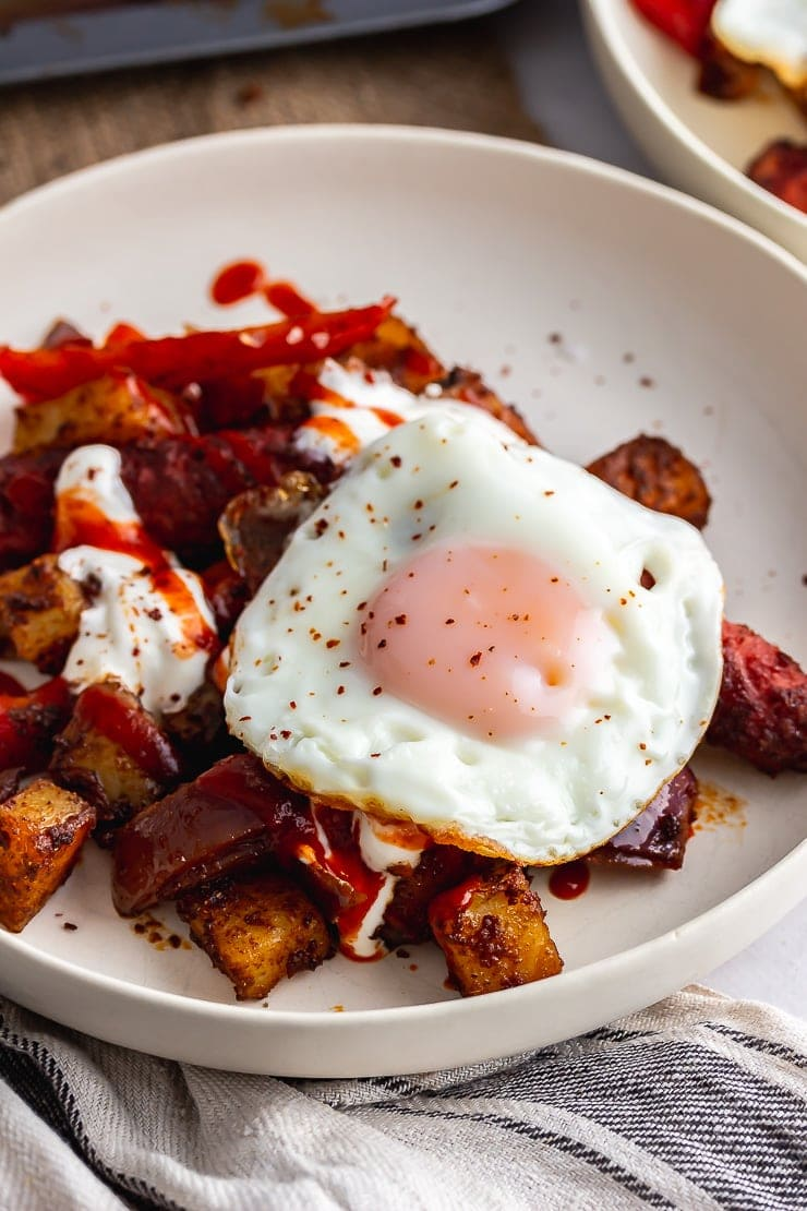 Close up of veggie sausage bake in a white bowl topped with a fried egg