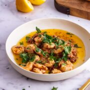 White bowl of chilli prawns on a marble background