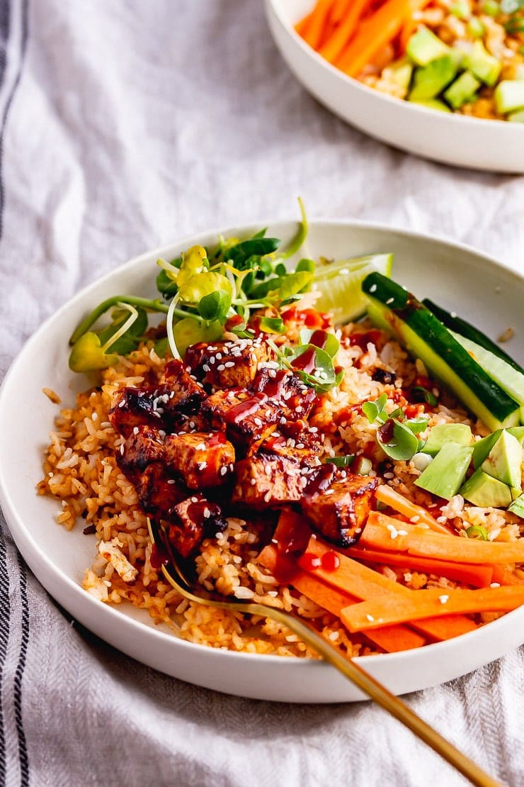 Spicy ruce bowls topped with tofu and vegetables and hot sauce
