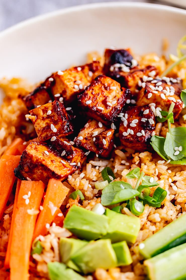 Close up of tofu and vegetables in a spicy rice bowl