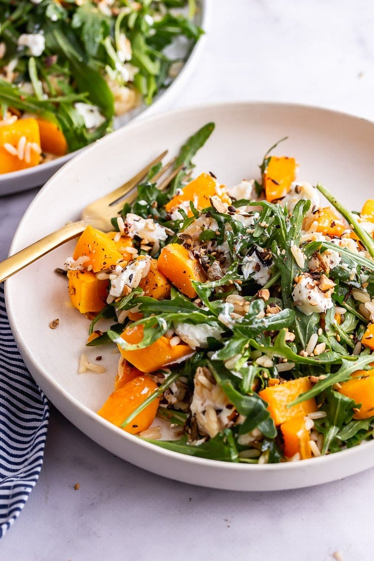 Bowl of butternut squash salad with a gold fork