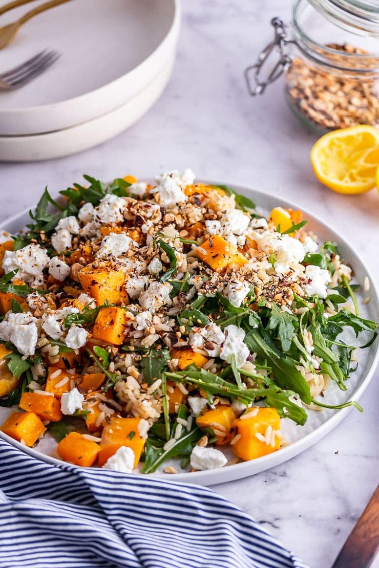 Platter of butternut squash salad on a marble background