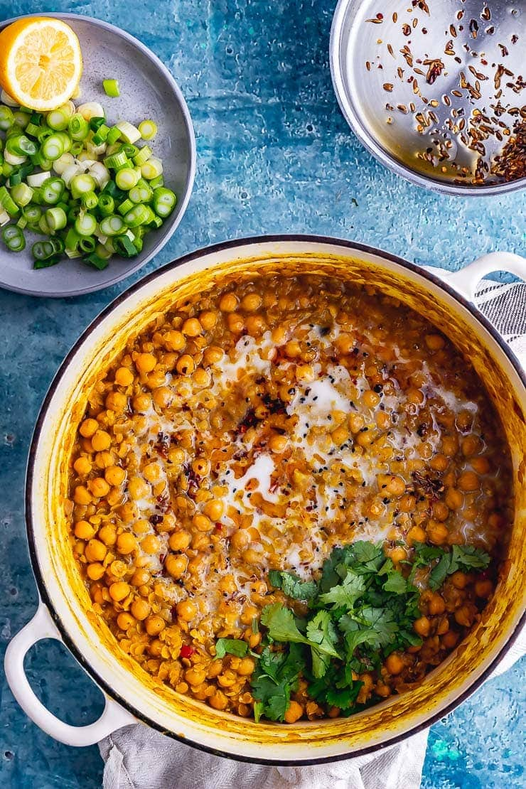 Overhead shot of chickpea curry in a white pot with spring onion and lemon