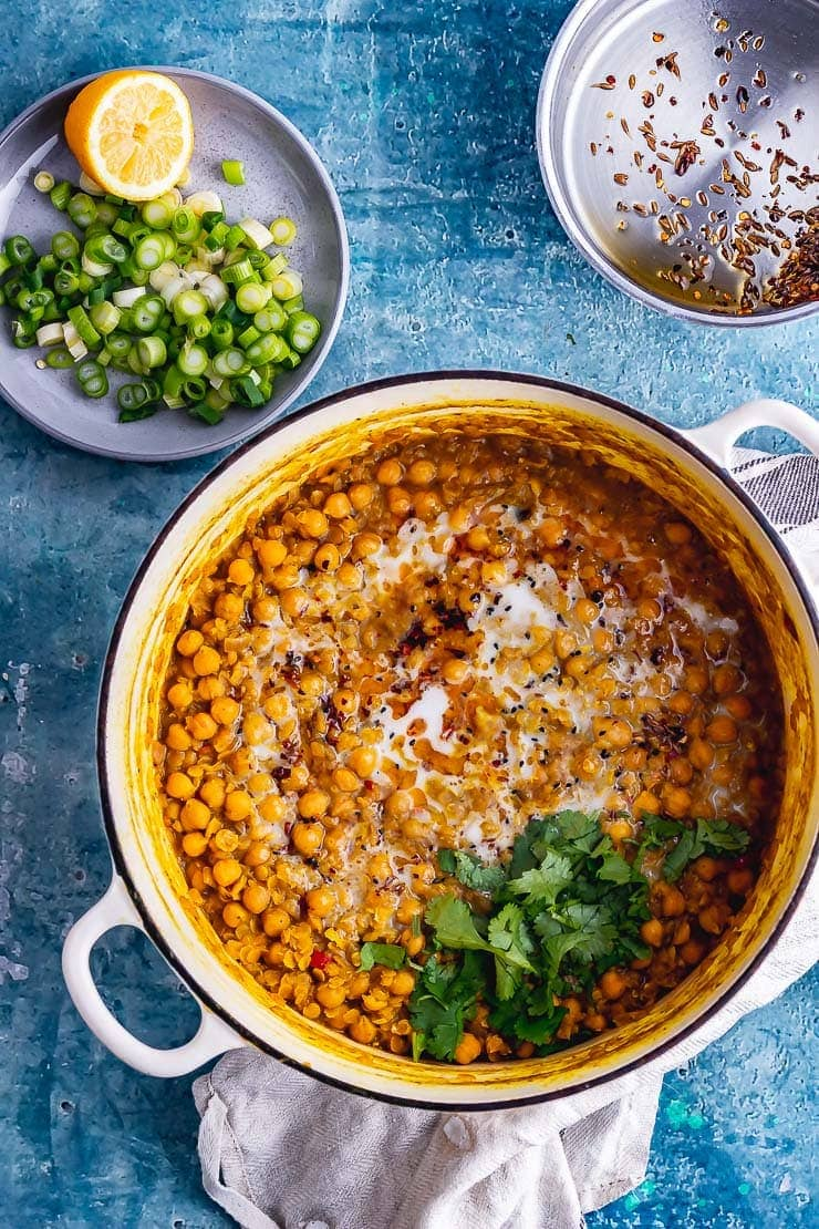 Overhead shot of a white pot of chickpea curry on a blue background