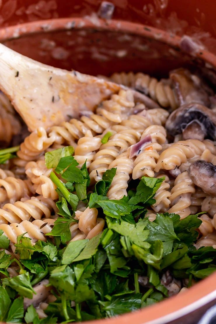 Close up of pressure cooker creamy mushroom pasta with a wooden spoon