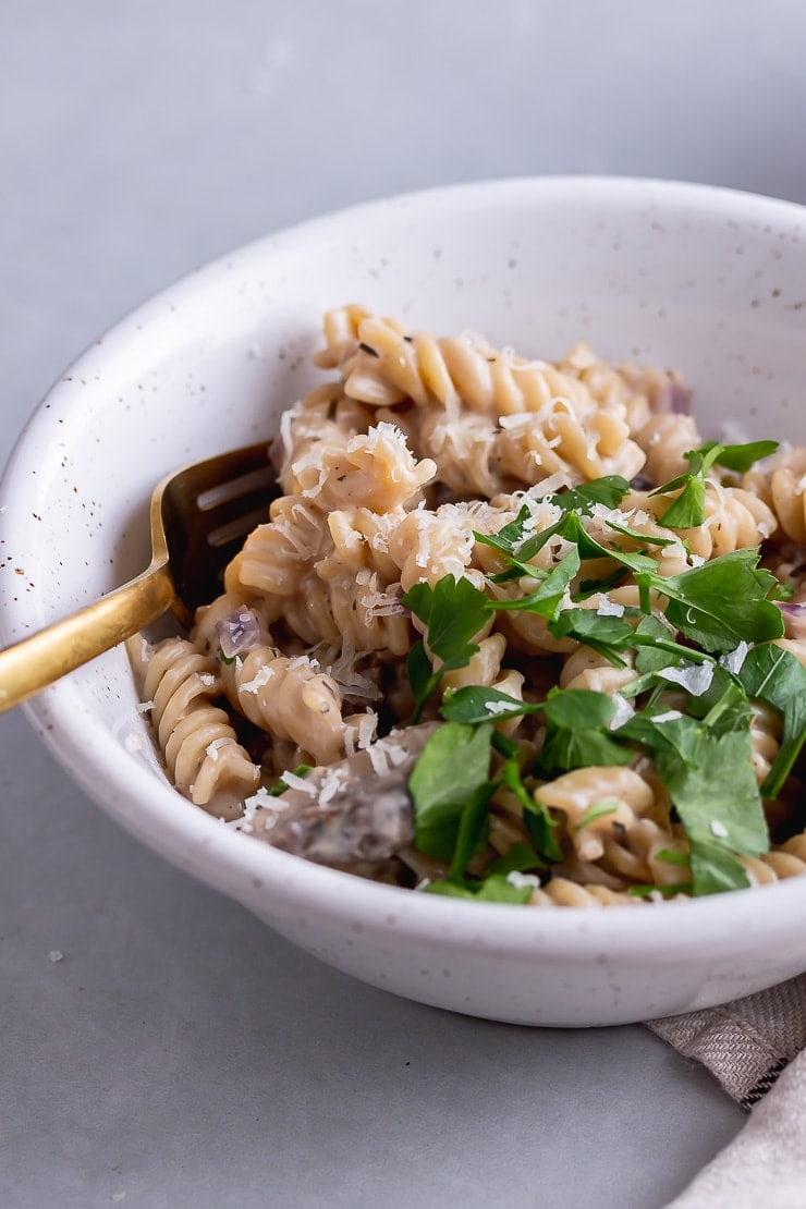White bowl of pressure cooker creamy mushroom pasta on a grey background