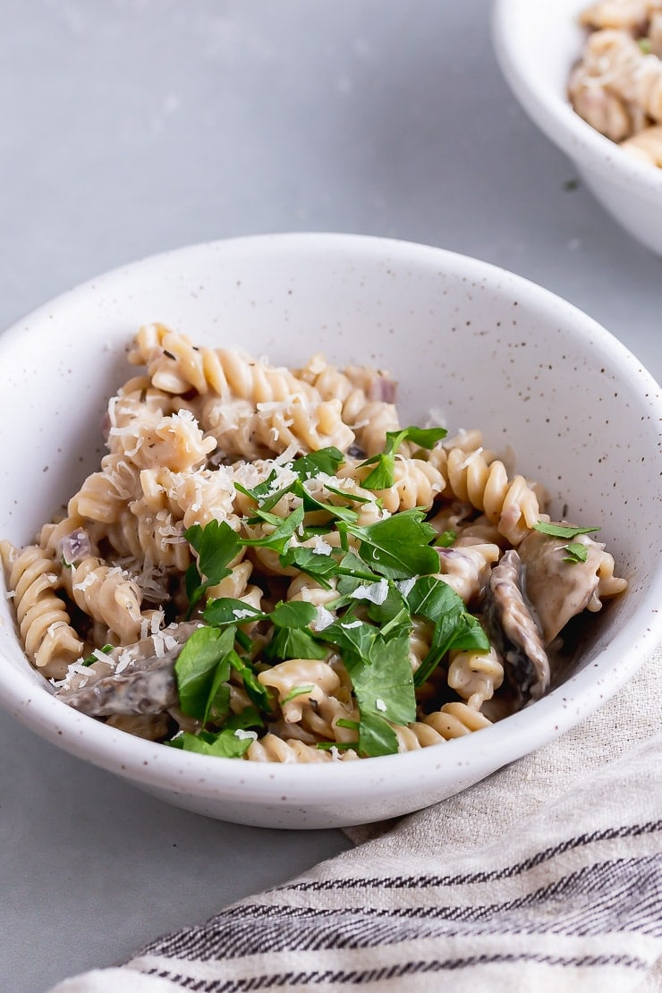 White bowl of pressure cooker creamy mushroom pasta on a grey surface