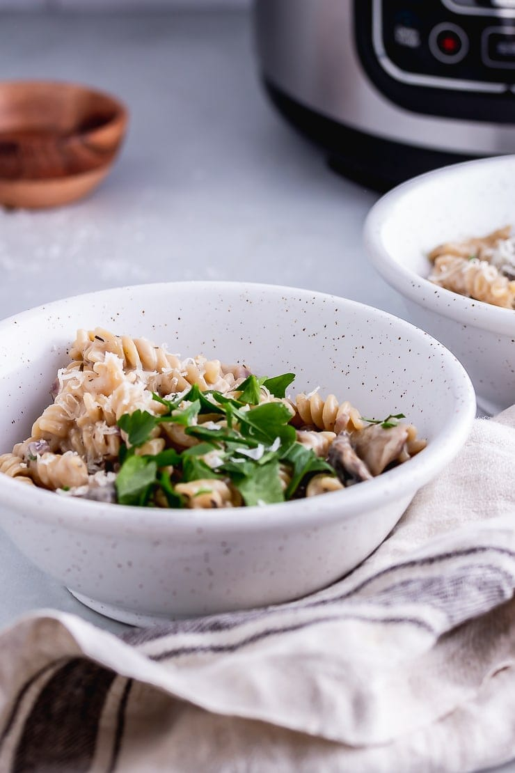 Side on shot of pressure cooker creamy mushroom pasta in a white bowl with a cloth