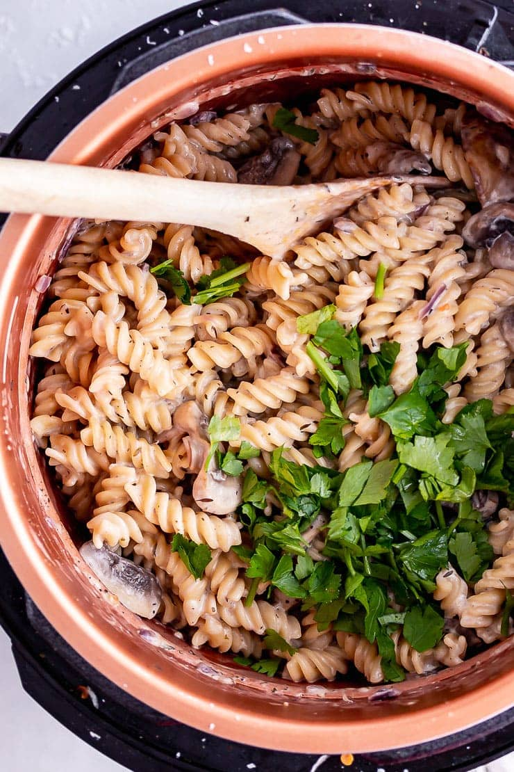 Overhead shot of pressure cooker creamy mushroom pasta with a wooden spoon and parsley