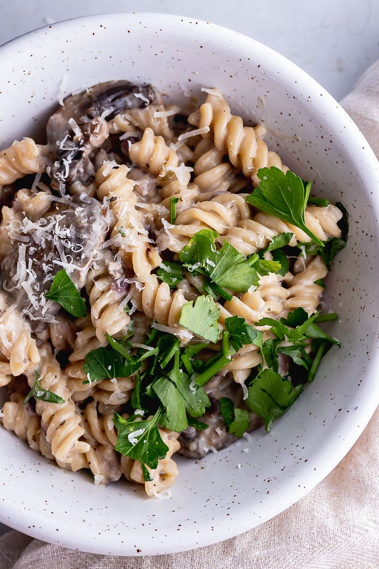 Close up of pressure cooker creamy mushroom pasta in a white speckled bowl