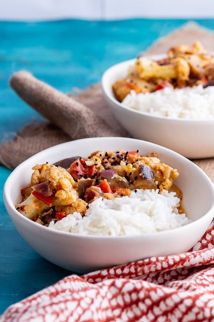 White bowls of pressure cooker vegetable curry on a blue background