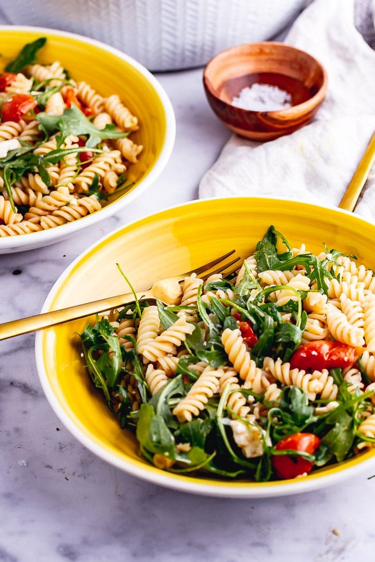 Yellow bowl of roasted tomato pasta salad with a gold fork