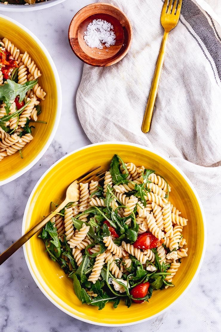 Overhead shot of roasted tomato pasta salad in yellow bowls