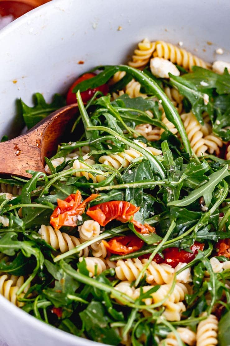 Close up of roasted tomato pasta salad with rocket and a wooden spoon