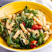 Yellow bowl of roasted tomato pasta salad on a marble background