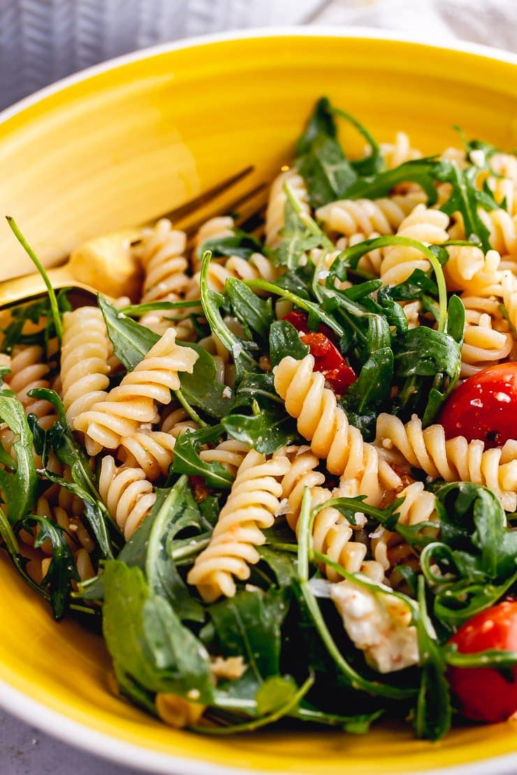 Close up of roasted tomato pasta salad in a yellow bowl